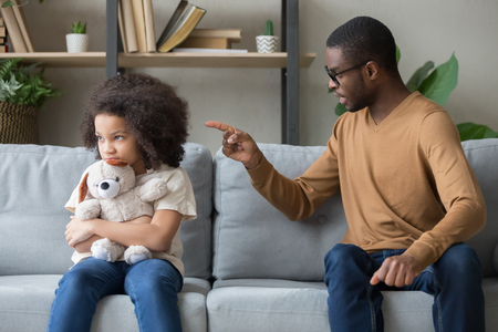 Foto de Angry african father sitting with little stubborn daughter holds stuffed toy feels upset, dad scolds for discipline bad behaviour capricious kid, family generations problems, misunderstanding concept - Imagen libre de derechos