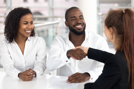 Foto de Happy black couple satisfied clients customers handshake bank manager insurer broker take loan buy insurance, african american family buyers signing mortgage investment contract shake realtor hand - Imagen libre de derechos