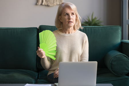 Foto de Mature grey haired woman suffering from heat stroke, sweating, high temperature at home, sitting on couch, waving fan, using laptop, middle aged female cooling in hot weather, feeling uncomfortable - Imagen libre de derechos