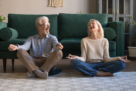 Foto de Happy mature couple having fun, practicing yoga together at home, laughing grey haired man and woman sitting in lotus pose on floor in living room, breathing, relaxing, healthy lifestyle concept - Imagen libre de derechos