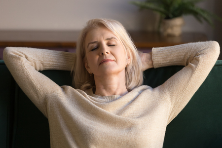 Photo for Calm middle aged woman relaxing enjoying weekend on comfortable sofa, grey haired carefree grandmother with hands behind head daydreaming, breathing, no stress peaceful free time at home close up - Royalty Free Image