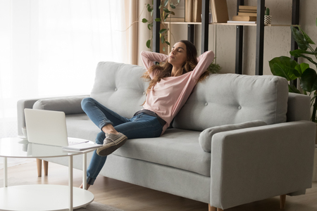 Photo for Relaxed young woman leaned on couch closed eyes putting hands behind head enjoy fresh air, freelancer resting from work in modern cozy living room alone, daydream day nap, fall asleep or pause concept - Royalty Free Image