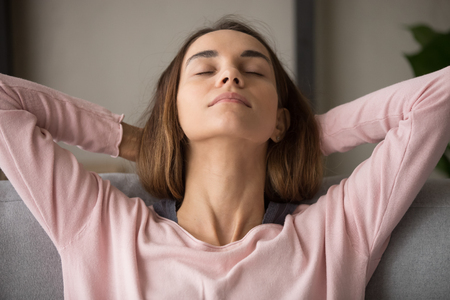 Photo for Close up front view attractive woman face with closed eyes leaning resting on sofa hold hands behind head fall asleep day nap feels serenity and placidity. No stress, inner harmony and balance concept - Royalty Free Image