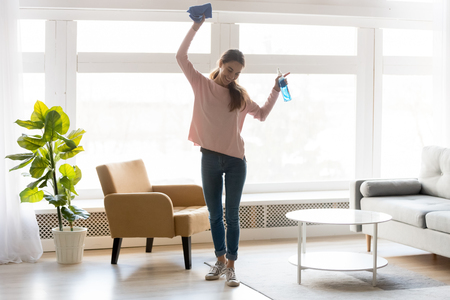 Foto de Full-length woman in casual clothes dance do house cleaning holds blue rag spray bottle detergent feels happy, qualified housekeeping specialist agency hiring, quick fast and easy home chores concept - Imagen libre de derechos