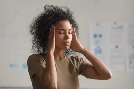 Foto de Close up of exhausted african American woman feel unwell touch massage temples suffer from headache, tired black female worker have migraine or dizziness stand with eyes closed. Health problem concept - Imagen libre de derechos