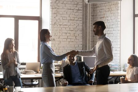 Photo for Company ceo handshaking congratulate young woman with successful work and promotion, supporting, appreciating for good result or rewarding while multi-ethnic business team gathered together in office - Royalty Free Image