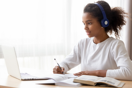 Photo pour African American teen girl wearing headphones learning language online, using laptop, looking at screen, doing school tasks at home, writing notes, listening to lecture or music, distance education - image libre de droit