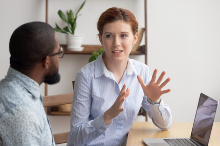 Photo pour Two diverse businesspeople chatting sitting behind laptop in office. Excited caucasian female sharing ideas or startup business plan with black male coworker. Informal conversation, work break concept - image libre de droit