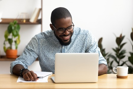 Foto de Smiling african-american manager sitting at office desk using laptop looking at screen. Handsome man reading good news, making funny video call, chatting social network. Coffee break concept - Imagen libre de derechos