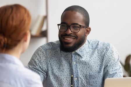 Foto de Two multiracial business partners speaking discussing sharing ideas. Focus on smiling male african-american colleague listening caucasian female candidate. Negotiation job interview conversation - Imagen libre de derechos
