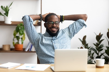 Photo for Smiling Afro-American businessman holding hands behind head sitting at office desk behind laptop. Happy black employee feeling no stress, relaxing, watching funny video after successful working - Royalty Free Image