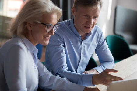 Photo pour Young businessman and mature woman working on computer project together, looking at screen, mentor, trainer explaining task to employee, using laptop app together, helping new worker with software - image libre de droit