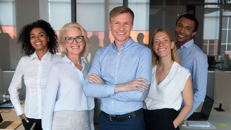 Photo for Successful team leader and diverse employees posing for photo together, smiling businesspeople looking at camera, standing in modern office, feeling proud, multiracial company staff photo - Royalty Free Image