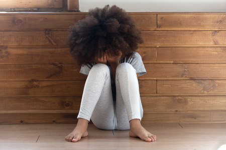Photo pour Sad stressed little african american girl crying, upset lonely bullied child feels abandoned abused, preschool black orphan kid in tears sit alone on floor, children abuse, unhappy childhood concept - image libre de droit