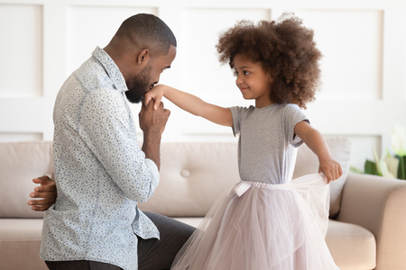 Foto de Loving young african american dad standing on knee thanking cute little child daughter for dance, happy black father play with small kid girl princess holding kissing hand having fun at home together - Imagen libre de derechos