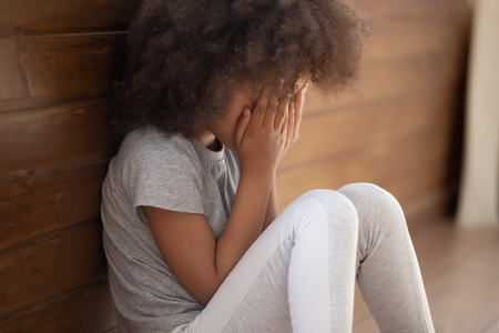 Photo pour Upset small african american child girl crying covering face with hands sitting alone on floor, sad lonely orphan kid being bullied abused feeling stressed or scared, children violence abuse concept - image libre de droit