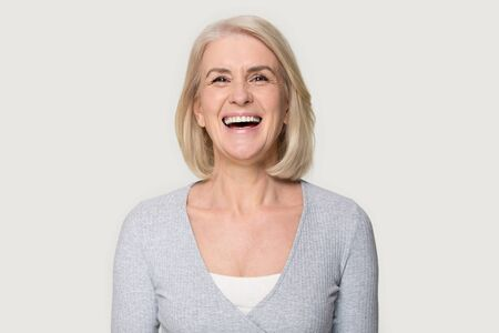 Foto de Head shot portrait overjoyed blond middle aged female smiling look at camera laughing feels happy pose isolated on grey studio background, advertise clinic procedure dental care prosthesis for seniors - Imagen libre de derechos