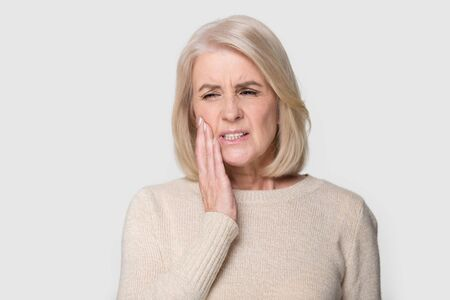 Foto de Head shot studio portrait senior blond female pose on grey white background, touches cheek suffering from sudden tooth pain feels unhealthy unhappy need dental service help, medical insurance concept - Imagen libre de derechos