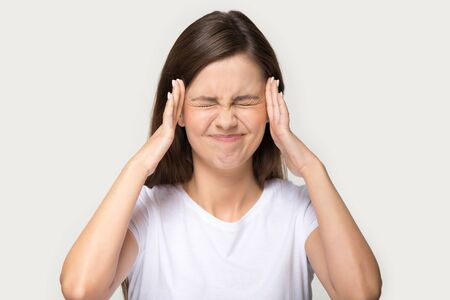 Foto de Head shot portrait isolated on grey background millennial frown woman closed eyes touch temples suffers from pounding throbbing tension headache, hate noise feels discomfort unwell unhealthy concept - Imagen libre de derechos