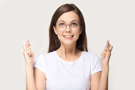 Foto de Comical woman in glasses looks up cross fingers asks for good luck, wish for chance, pose on grey background studio head shot portrait, student girl hope for passing exam, let dream come true concept - Imagen libre de derechos