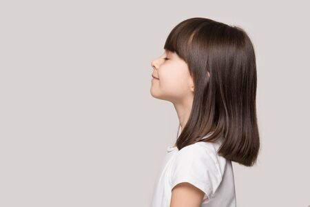 Photo pour Profile side view face brown-haired little girl standing isolated on beige studio background, preschool kid do deep breath enjoy fresh air or dreaming fill with energy feeling healthy and good concept - image libre de droit