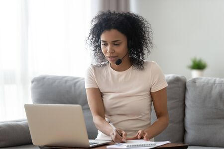 Foto de Young african woman wearing wireless headset looking at laptop making notes, focused black girl student teacher watching webinar online training talking by video conference call, e learning concept - Imagen libre de derechos