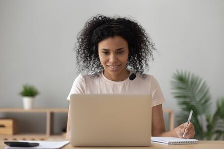 Foto de African american woman student wear wireless headset e learning making notes looking at laptop sit at home office desk, black girl study online making video call watching webinar, distance education - Imagen libre de derechos