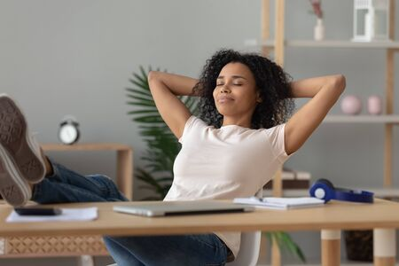 Photo for Happy calm african girl student relaxing holding hands behind finished study work breathing fresh air sit at home office desk feel stress relief stretching doing exercise dreaming enjoy peace of mind. - Royalty Free Image