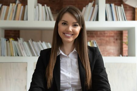 Foto de Smiling young business woman in suit coach teacher looking at camera at distant job interview, confident female professional looking at webcam talking make conference call doing internet video chat - Imagen libre de derechos