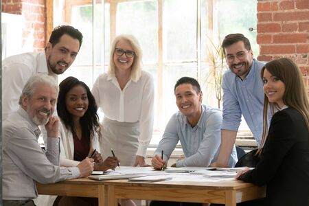 Foto de Professional business team young and old people posing together at office table, happy diverse leaders employees looking at camera, smiling multiracial staff corporate people workers group portrait - Imagen libre de derechos