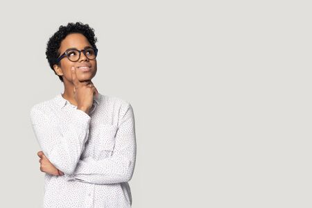Photo for Thoughtful african American girl in glasses isolated on grey studio background look up at blank copy space aside, pensive biracial millennial woman think pondering over sale offer making choice - Royalty Free Image