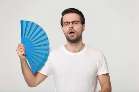 Foto de Guy wearing gasses white t-shirt feels overheated holds blue waver fan induces airflow cooling himself reducing heat pose isolated on gray studio background, summer weather, no air conditioner concept - Imagen libre de derechos