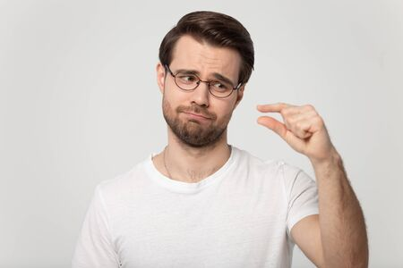 Foto de Head shot portrait guy isolated on grey background wearing glasses look at hand showing with fingers something small feels disappointed pity about little size insufficient length or thickness concept. - Imagen libre de derechos