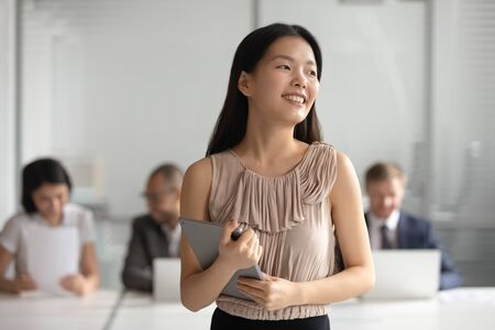 Foto de Happy dreamy young asian businesswoman holding digital tablet looking away dream of successful career, plan new goals, think about future hope for new opportunities in office, business vision concept - Imagen libre de derechos