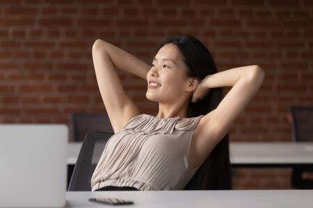 Photo pour Happy positive calm asian business woman employee student relax take break at work hold hand behind head sit at office desk rest from computer stretch feel no stress relief peace of mind at workplace. - image libre de droit