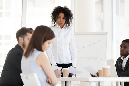 Photo pour Angry African American businesswoman, boss scolding female young worker, intern for bad work results, holding business briefing, lecturing employee, subordinate for business failure at company meeting - image libre de droit