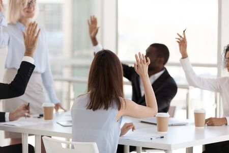 Photo pour Rear view, employees involved in team building activity, raised hands, mature female coach, mentor holding business briefing, staff training, business trainer interact with diverse office workers - image libre de droit