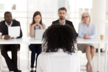 Photo for African American female applicant at job interview rear view, diverse team of HR managers, recruiters listening to woman candidate for vacancy answering questions, making decision, employment concept - Royalty Free Image