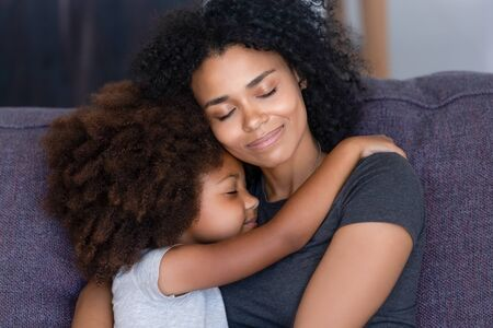 Photo pour Close up biracial family portrait loving mother and little daughter sitting on couch at home hugging with closed eyes. Love, new mom for adopted child, warm relationships, caring elder sister concept - image libre de droit
