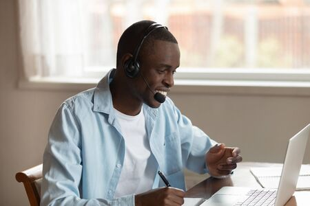 Photo pour Smiling african guy wear headset holds pen writes in notepad studying online having lesson interact with tutor distantly using pc, millennial black man watch video seminar noting data feels satisfied - image libre de droit