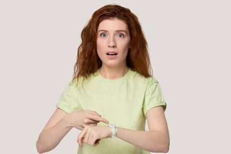 Photo pour Head shot studio portrait over grey background stressed red-headed woman feels shocked missed meeting or appointment, girl pointing finger on wrist watch checking time concept of late urgent and hurry - image libre de droit