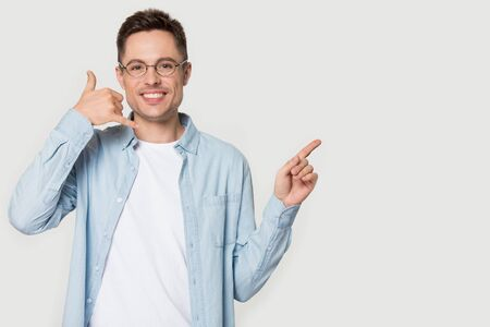 Foto per Man in glasses blue shirt smiling look at camera makes call me gesture points finger aside at announcement pose on grey white blank, copy space for advertisement text, connection communication concept - Immagine Royalty Free