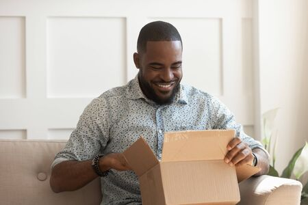 Photo pour Smiling african american man consumer open cardboard box get postal parcel, happy black male customer receive carton package sit on sofa at home satisfied with fast shipment online purchase delivery - image libre de droit