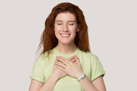 Photo pour Head shot studio portrait grateful red-headed woman in green t-shirt closed her eyes smiling holds hands on chest pose on grey white background, cupped arms as symbol of sincere feelings appreciation - image libre de droit