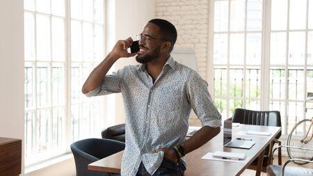 Foto de Happy african american businessman standing in modern work space talking on phone, smiling young black entrepreneur startup owner speak on cellphone enjoy mobile conversation in creative office - Imagen libre de derechos