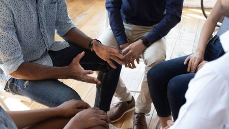 Foto de African man counselor therapist coach psychologist speak at group counseling therapy session concept encourage support patients in addiction talk share problem sit in circle in rehab, close up view - Imagen libre de derechos