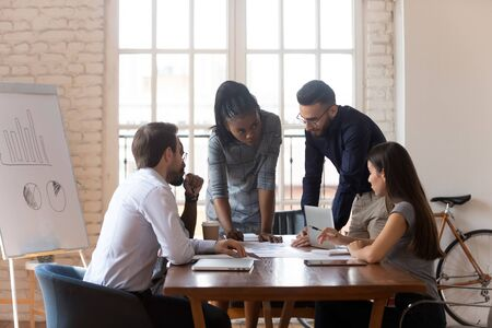 Foto de Multiracial business team diverse workers group cooperating brainstorm discussing paperwork share ideas on marketing plan working in teamwork at corporate meeting gather at office table in boardroom. - Imagen libre de derechos