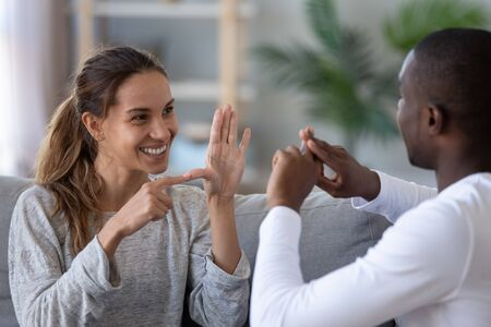 Foto de Smiling mixed ethnicity couple or interracial friends talking with sign finger hand language, happy two deaf and mute hearing impaired people communicating at home sit on sofa showing hand gestures - Imagen libre de derechos