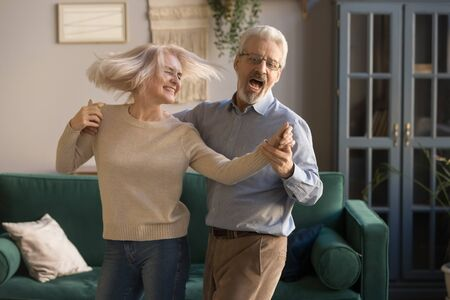 Foto de Carefree happy active old senior couple dancing jumping laughing in living room, cheerful retired elder husband holding hand of mature middle aged wife enjoy fun leisure retirement lifestyle at home - Imagen libre de derechos