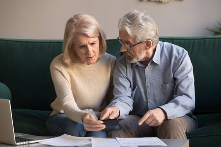 Foto de Serious stressed senior old couple worried about paperwork discuss unpaid bank debt calculate bills, shocked poor retired family looking at calculator counting loan payment upset about money problem - Imagen libre de derechos